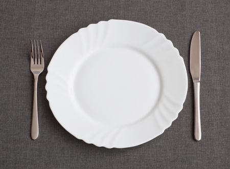 Set of utensil for dinner: plate, fork and knife photo