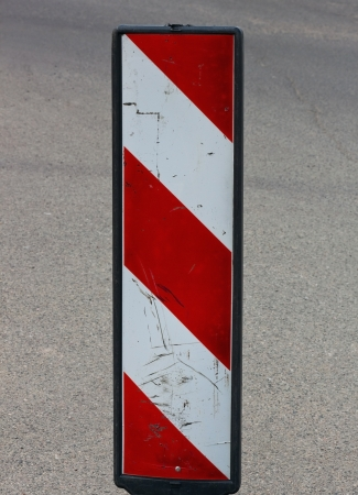 Road construction sign with red and white lines photo
