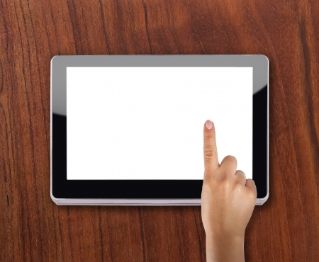 Modern tablet device over wooden background with index finger touching screen Stock Photo - 13945988