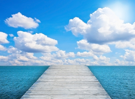 Pier on sunny day with white clouds Stock Photo