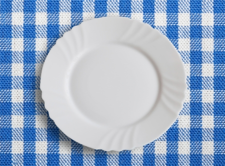 Lined white and blue dining cloth with plate photo