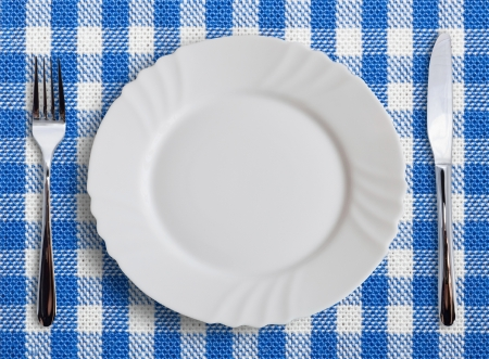 Lined white and blue dining cloth with plate and silverware photo