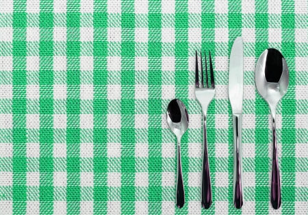 Lined white and blue dining cloth with silverware photo