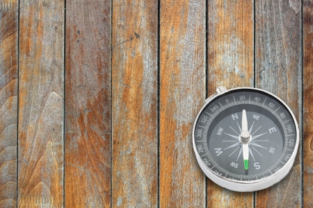 compas: Compass on the old wooden board surface