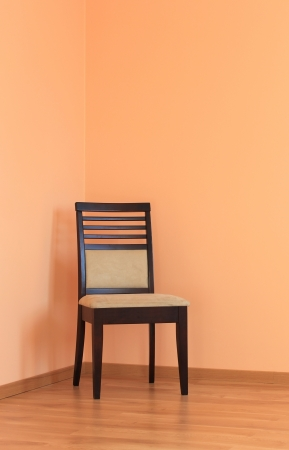 Empty floor and wall with one chair photo
