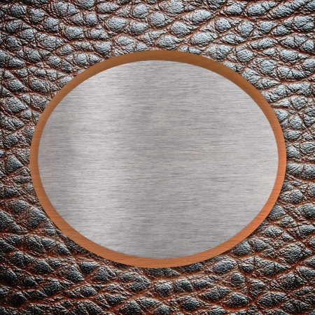 Metal plate on brown leather surface photo