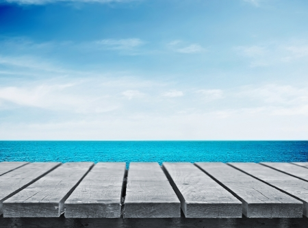 berth: Wooden gray pier on sunny day with blue sky