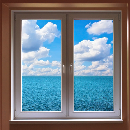 Windows with view to sea with cloudy sunny sky photo