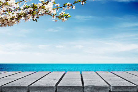 berth: Wooden table near sea with cherry branch