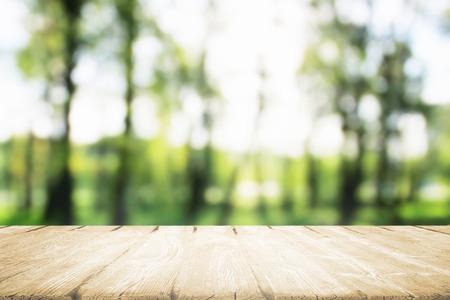 햇빛에 아침 공원에서 먹는 나무 테이블.