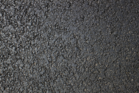 Dark fresh asphalt surface of the road