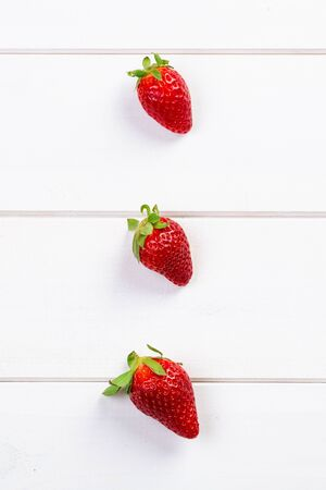 Three strawberries on wooden boards