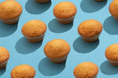 Muffins pattern on the blue table surface Imagens