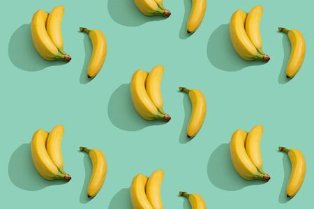 Ripe bananas pattern on the green background