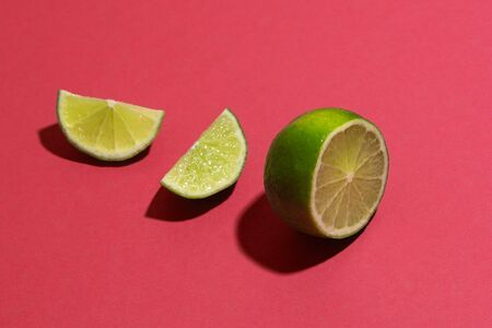 One ripe lime sliced on parts on color surface