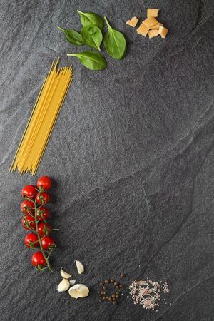 Pasta ingredients on the black slate background Imagens