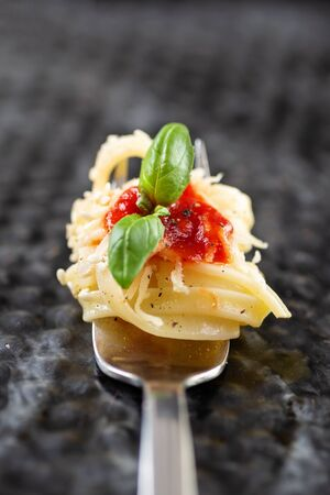 Pasta on fork with ketchup and basil leaf