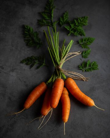 Bunch of fresh carrots on the black background