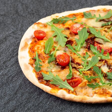 Juicy pizza on the table with cherry tomatoes and ruccola