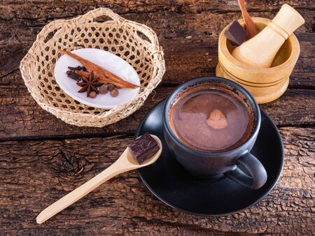 Cup of chocolate with spices (cinnamon, cloves and anise) and mortar on an authentic old table