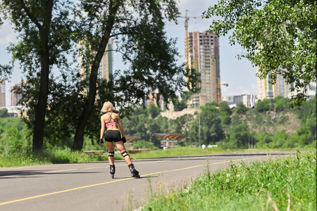 rollerblades: Fit, sporty and athletic young woman. Beautiful girl rollerblading on skates in a sportswear. Stock Photo