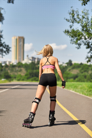 Fit, sporty and athletic young woman. Beautiful girl rollerblading on skates in a sportswear. Stock Photo