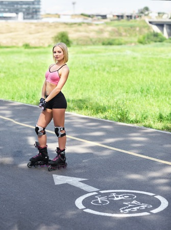 roller blade: Fit, sporty and athletic young woman. Beautiful girl rollerblading on skates in a sportswear. Stock Photo