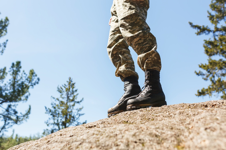 crampon: A man in camouflage old shoes with spikes for climbing on rocks. Trikoni. Tricouni