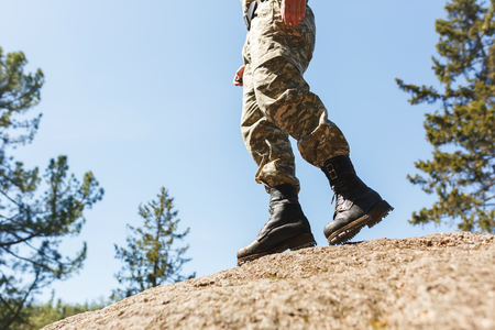 crampon: A man in camouflage old shoes with spikes for climbing on rocks. Trikoni. Tricouni.