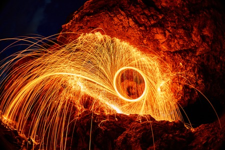 eyes are painted burning steel wool in the mountain
