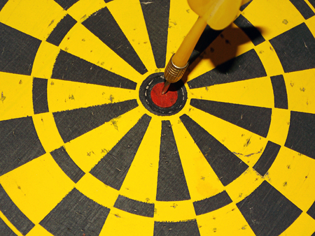 A yellow darts board and a yellow dart in the center.