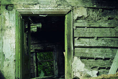 An open doorway abandoned and ruined hut. Stock Photo