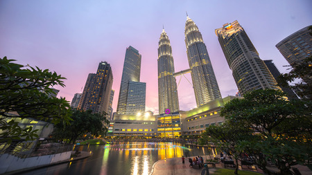 petronas: KUALA LUMPUR, MALAYSIA - AUGUST 1, 2015: Water Fountain at Suria KLCC with Petronas Towers and Office Buildings at Blue Hour sunset at Night. Its a popular shopping attraction to locals and tourists. Editorial