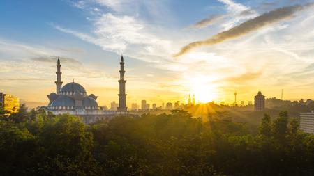 Sunrise op federaal Moskee Kuala Lumpur, met silhouet skyline van de stad Stockfoto