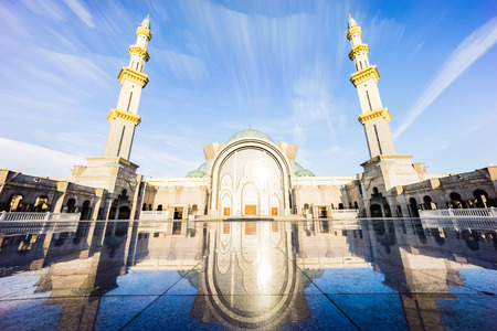 prayer tower: The external wall of the mosque turn yellowish as it hit by the light of the sunrise Stock Photo