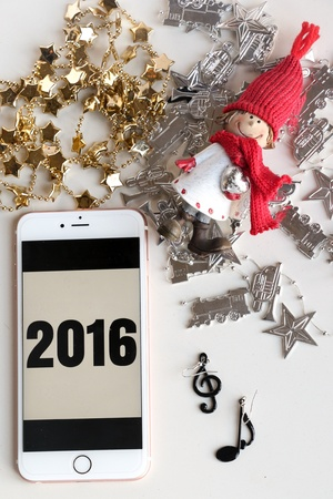silver: 2016 written on apple devices, iphone 5s, iphone6s, iphone 6s plus, ipad. Blach numbers on a white background. Christmas ornaments below. Overhead shot.