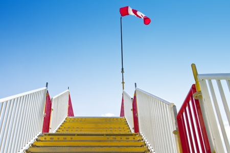 Yellow stairway with inflated windsock on its peak. photo