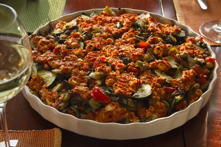 Vegetarian vegetable casserole with glass of white wine