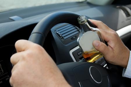 borracho: Controlador con una botella de alcohol se encuentra detrás del volante Foto de archivo