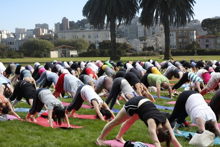 Big yoga group exercising on public ground