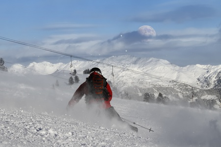 Skier is carving on a slope with daylight moon on horizon photo