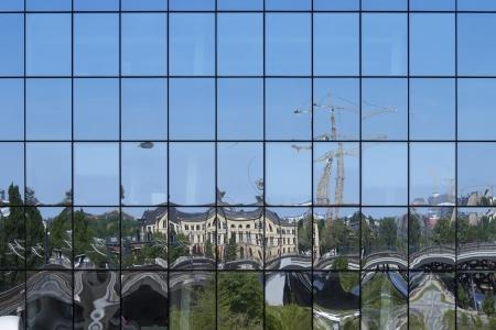 blue facades sky: City reflection on the facade of a building