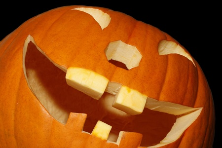 Grinning pumpkin lying diagonally in front of picture photo