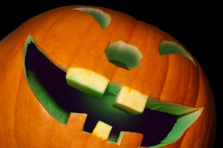Grinning pumpkin with green illuminated mouth. photo