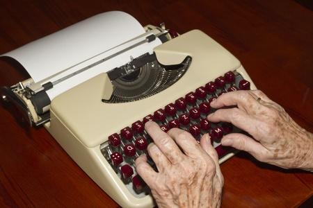 Elderly woman writes on a typewriter photo