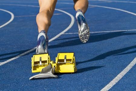 yellow block: Sprinter is starting from starting block Stock Photo