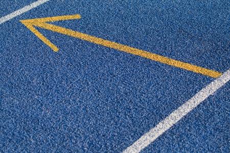 Blue tartan surface with yellow arrow Stock Photo - 10661184