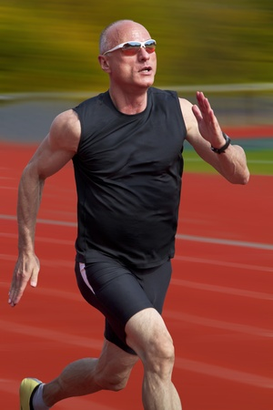 Male sprinter in middle age trains for race competition photo