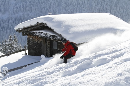 offpiste: Skier is skiing backcountry with blockhouse in the background