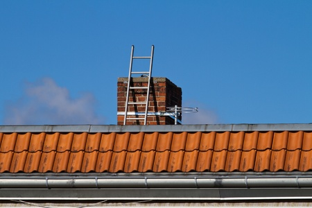 storied: Ladder is leaning on a chimney of a multi storied house